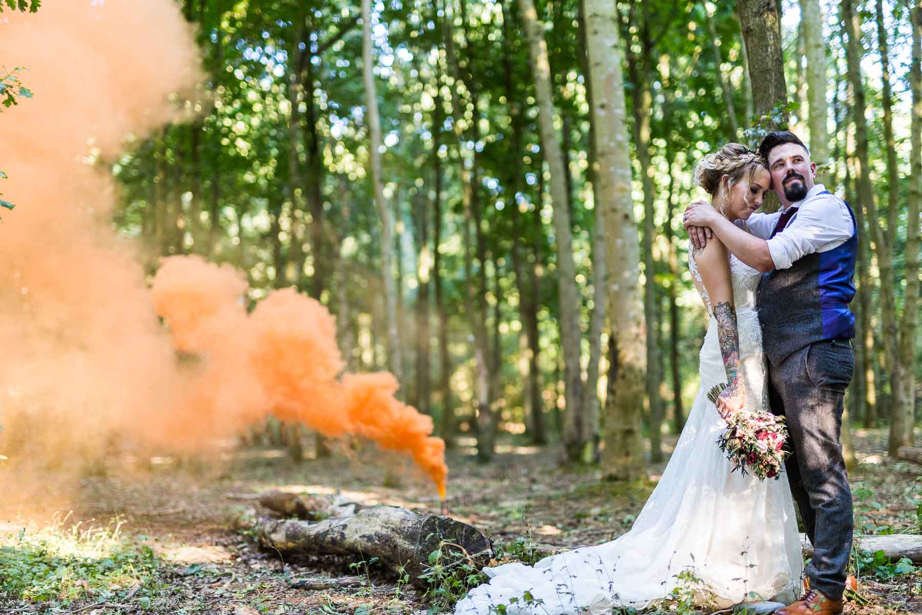 Wedding photo of a couple using a enola gaye smoke bomb on their wedding day in a wood in east hunsbury northampton
