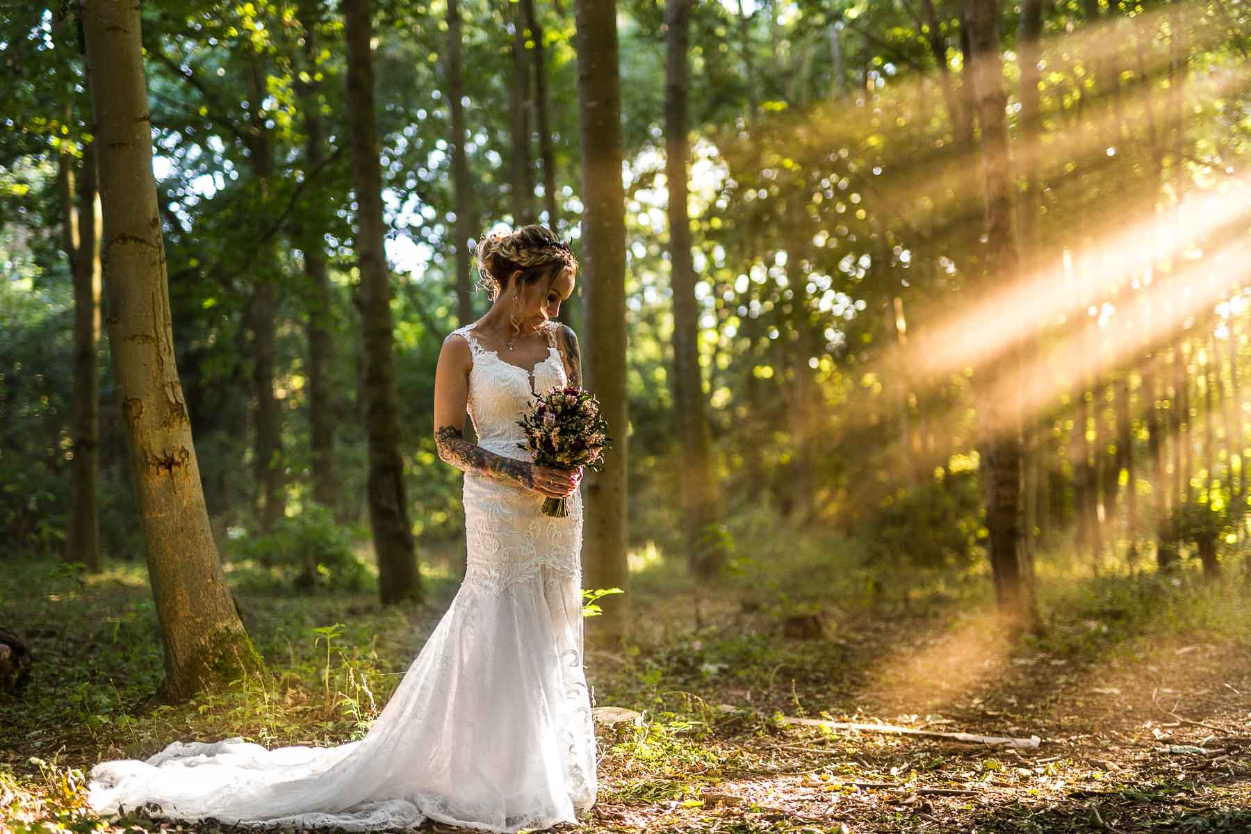 beautiful ethereal photo of a wedding bride in a wood in northampton, with sun beams piecing the woodland canopy