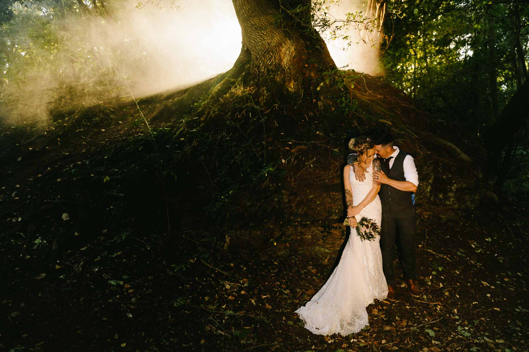Etheral wedding photo of the couple standing under a tree with mist underneath them