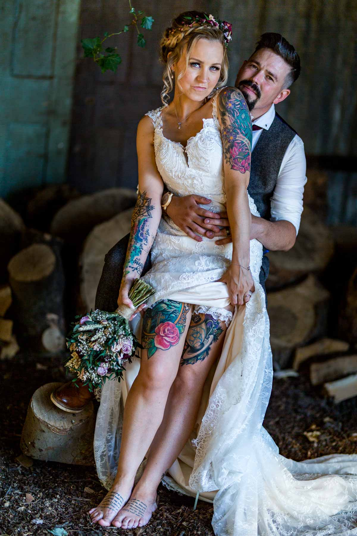 beautiful boho bride showing her tattoos in a moody photo taken in a old barn