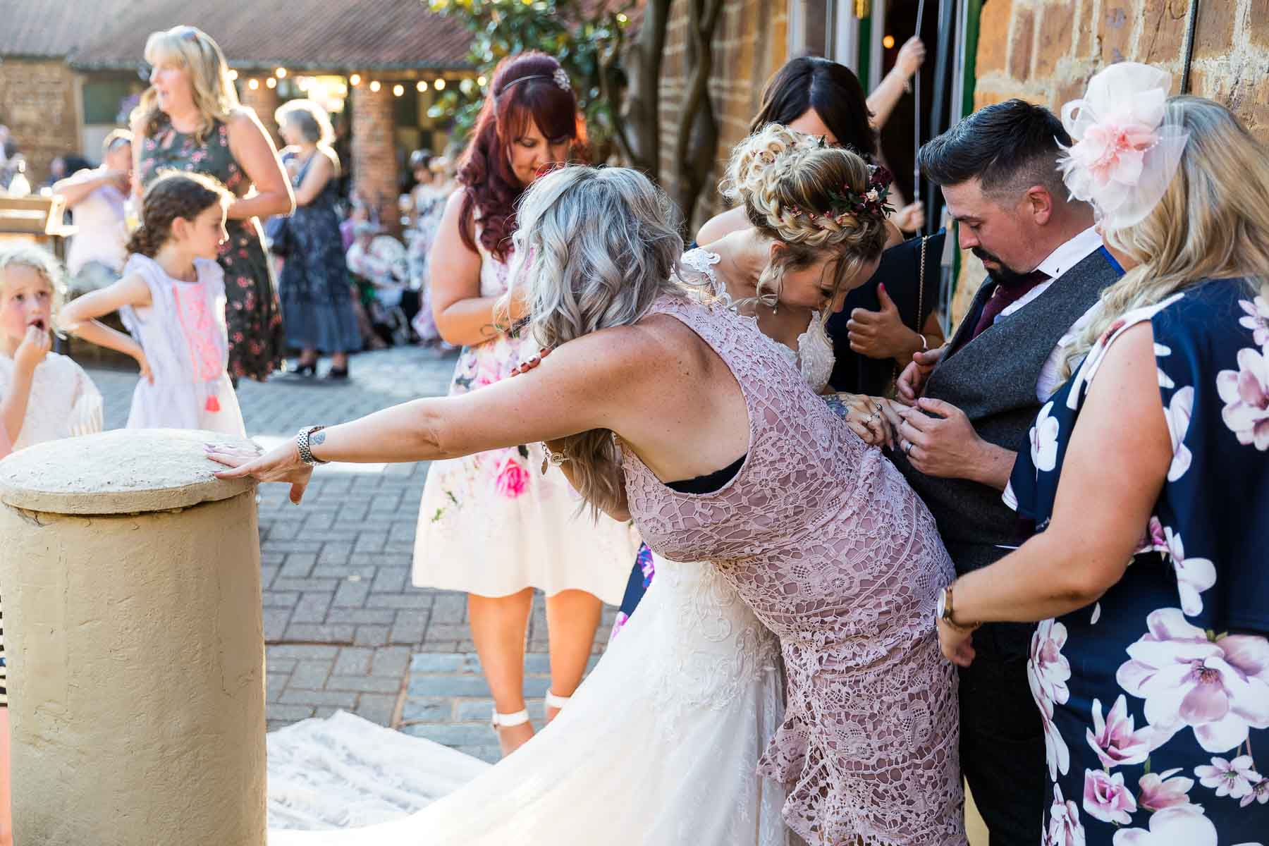groom awkwardly getting caught up in the dress of a guest