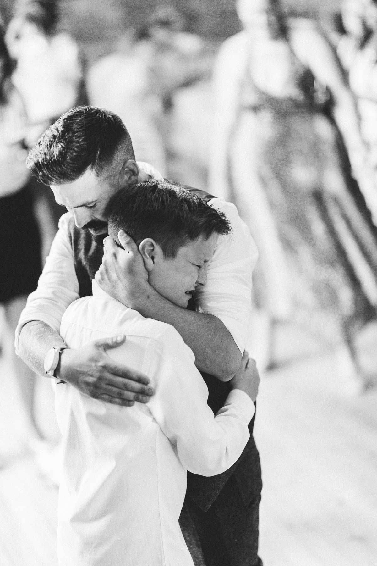 Groom hugging his son after the first dance