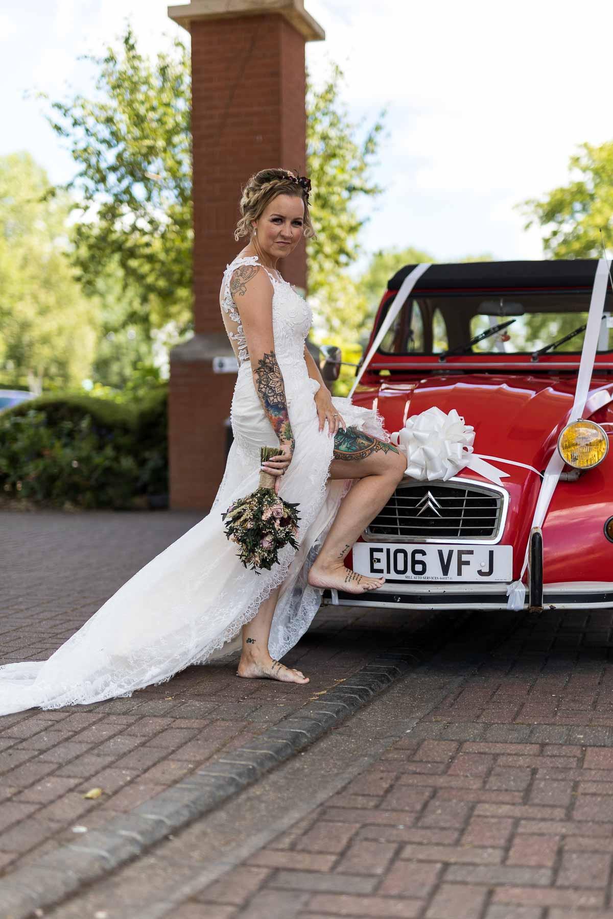 Bride posing with red citroen 2cv