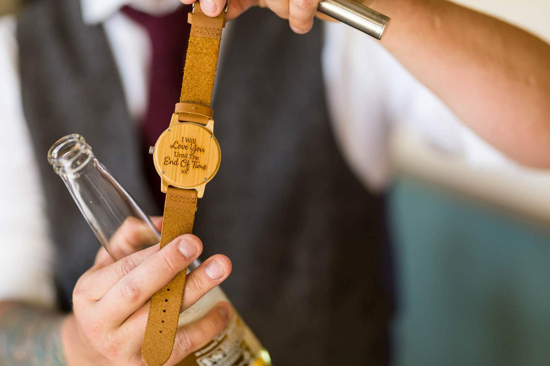 Groom holding his wooden watch with a message on the back