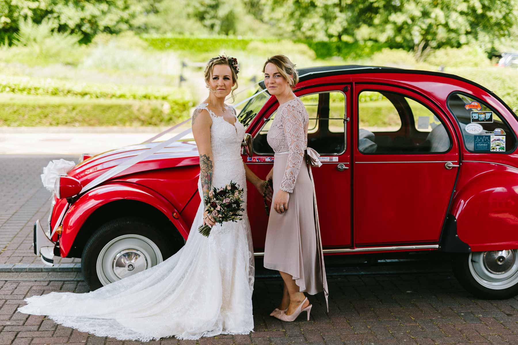 bride and sister posing with a red citroen 2cv