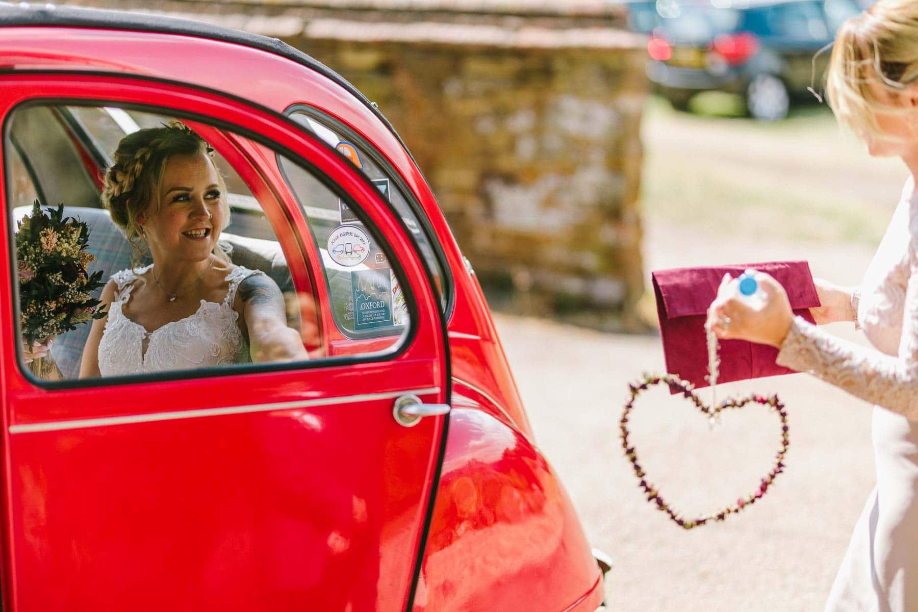 bride arriving in her red citroen 2cv