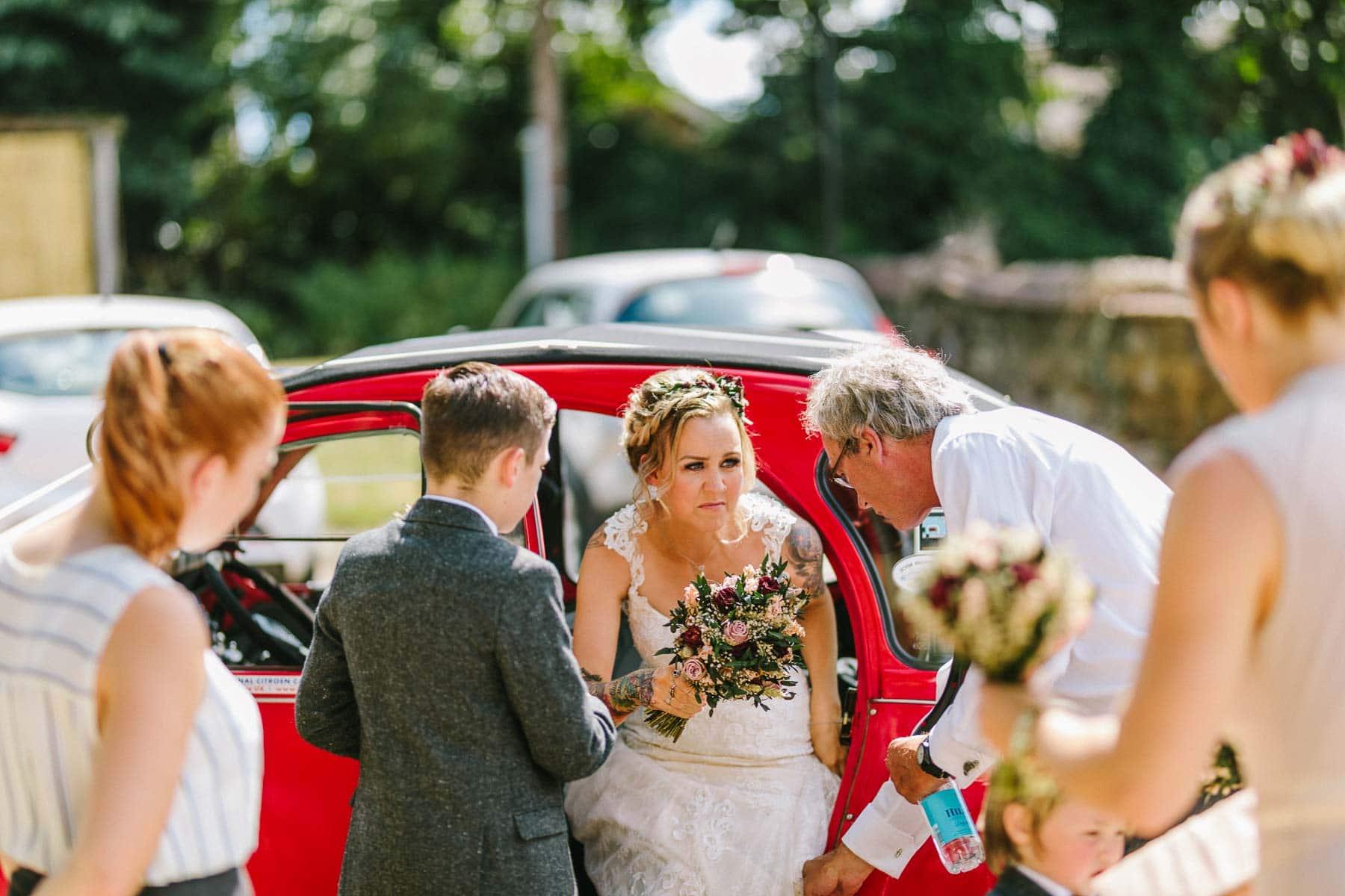 Bride leaving her red citroen 2cv
