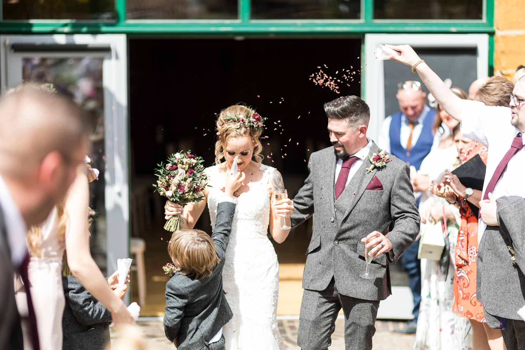 pageboy throwing confetti down the brides dress