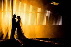 Bride and groom kissing in an Incredible barn wedding photo at Woodfarm wedding photographers northamptonshire