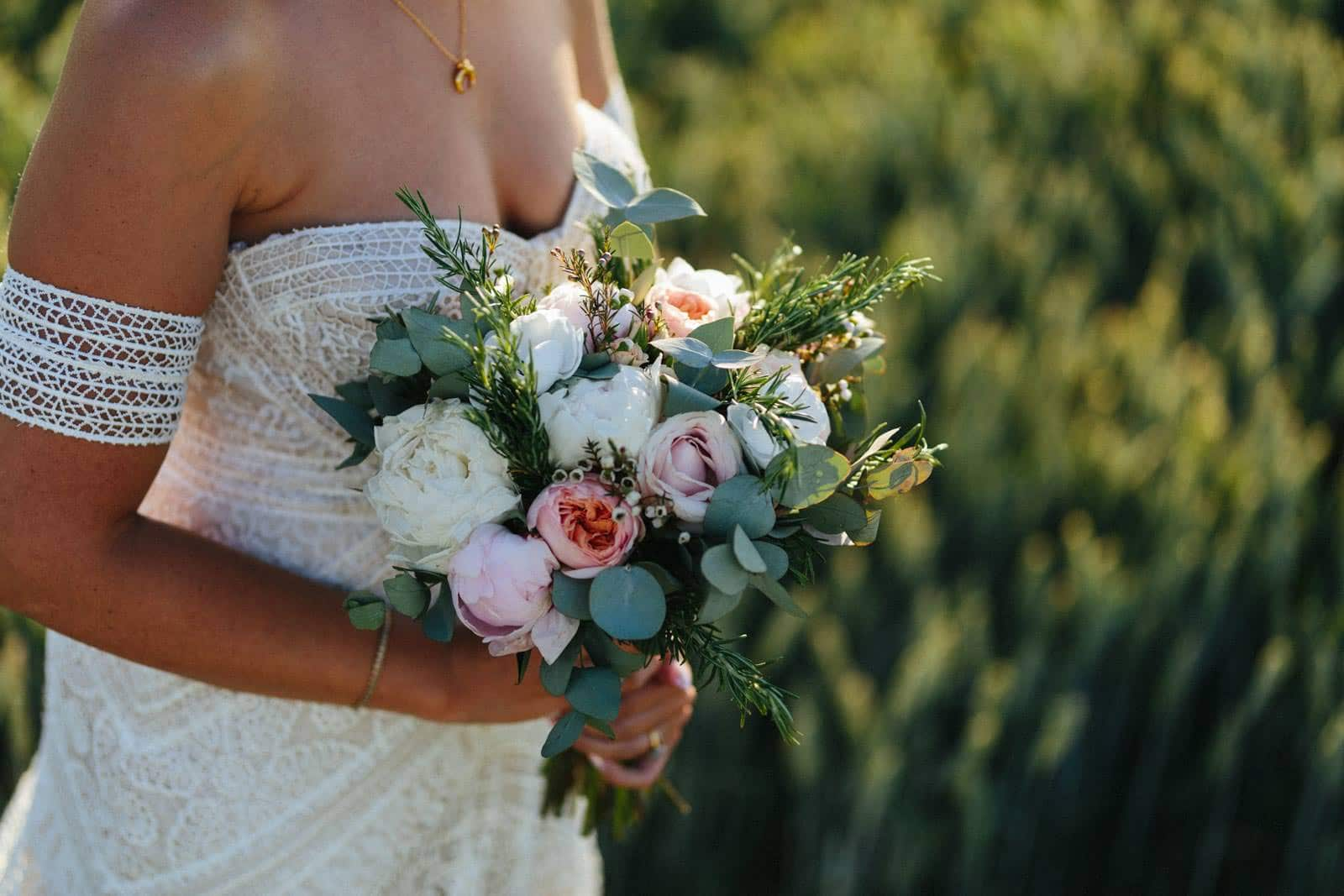 beautiful wedding flowers in a wheat field held by a boho bride