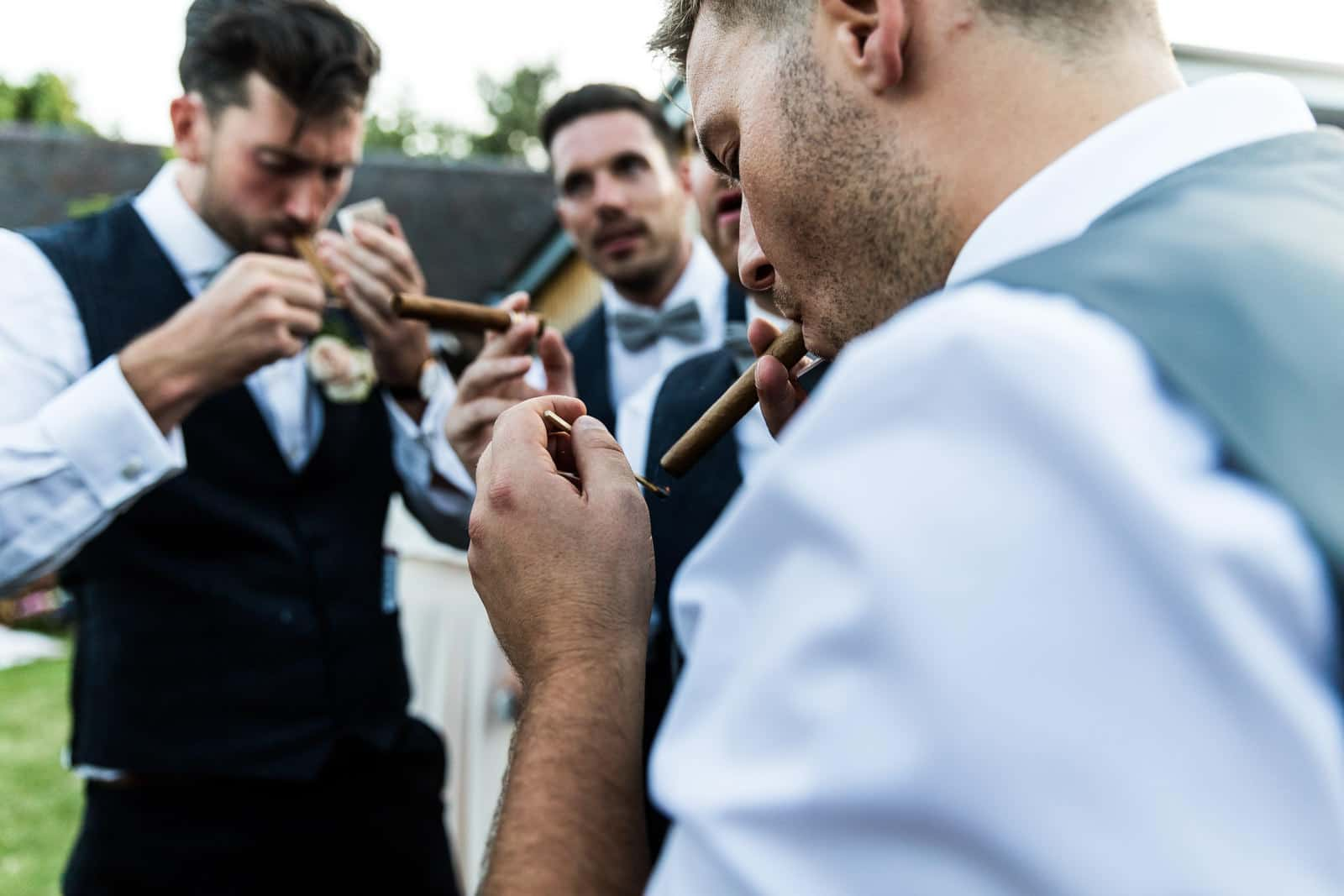 Groomsmen lighting cigars at a wedding at swallows nest barn