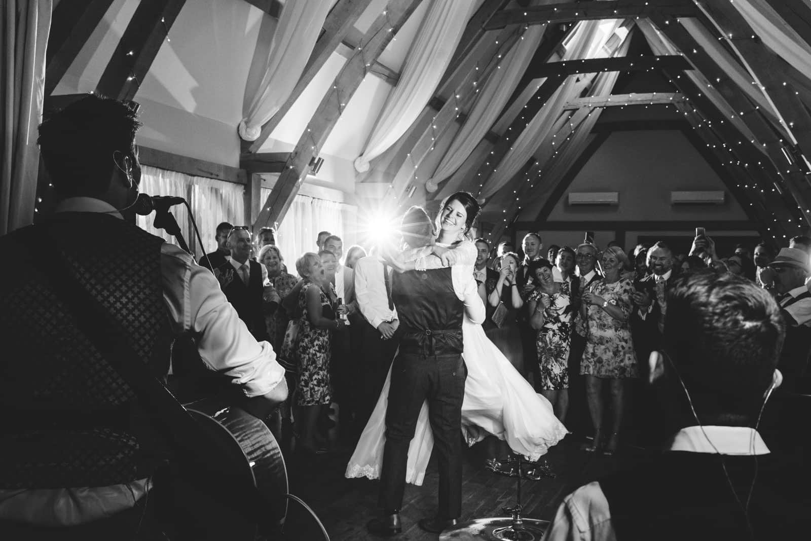 Beautiful first dance wedding photography moment as the bride is lifted up