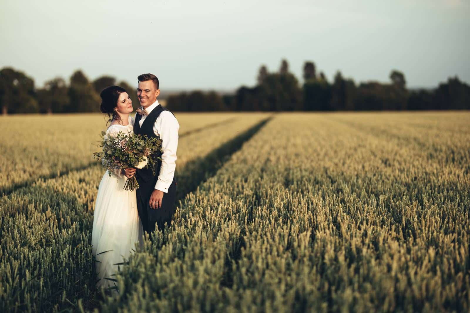 Bride and groom standing in a wheat field golden hour photography