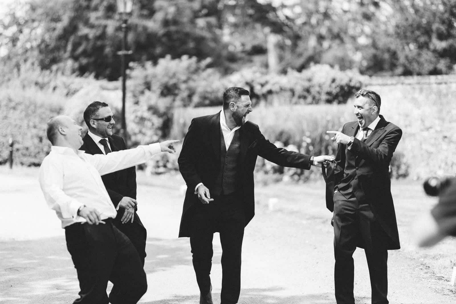 Groom and Groomsmen messing around and laughing having a good time