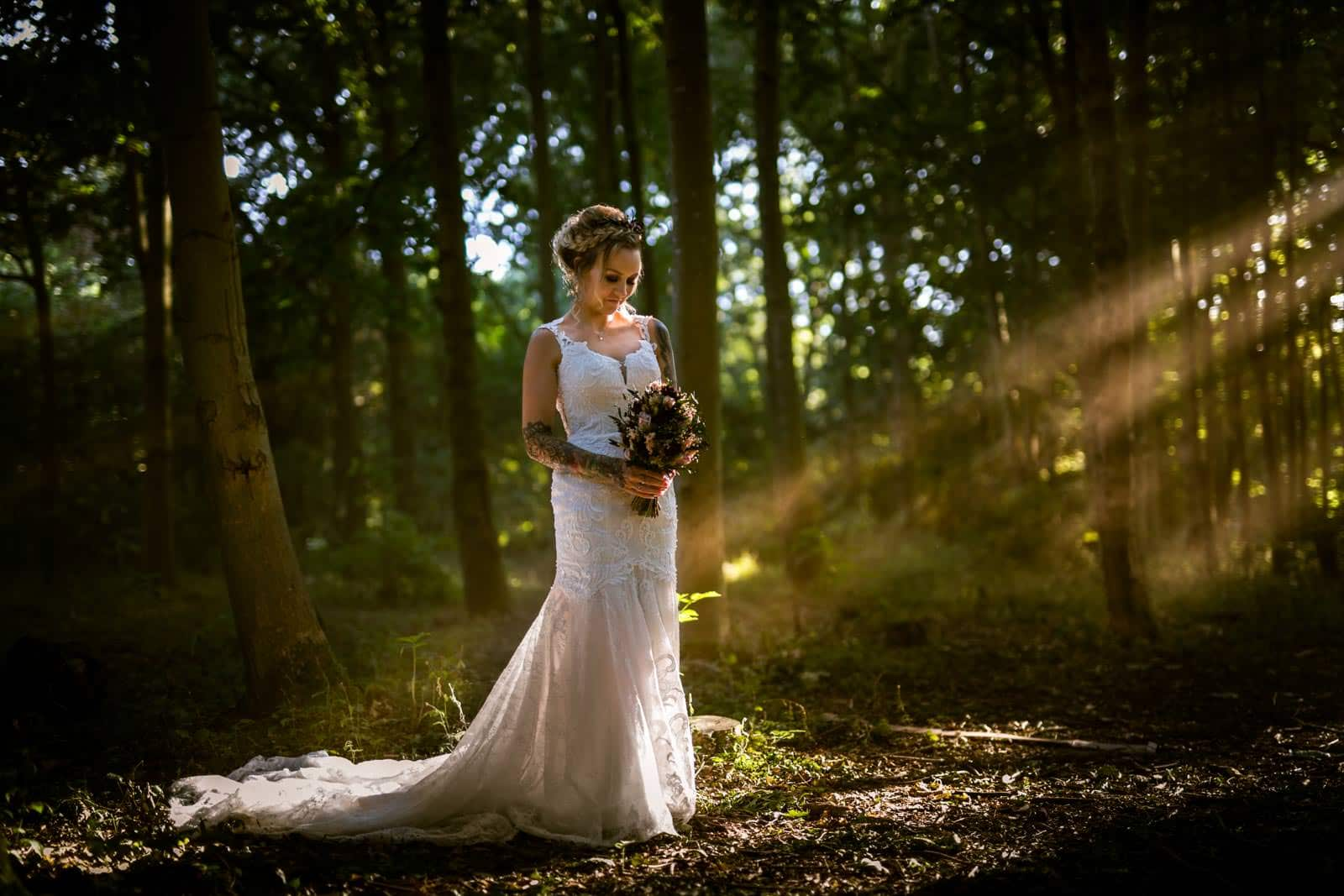 Beautiful photo taken at hunsbury hill center in Northampton. Bride standing in the forest being lit by sun beams