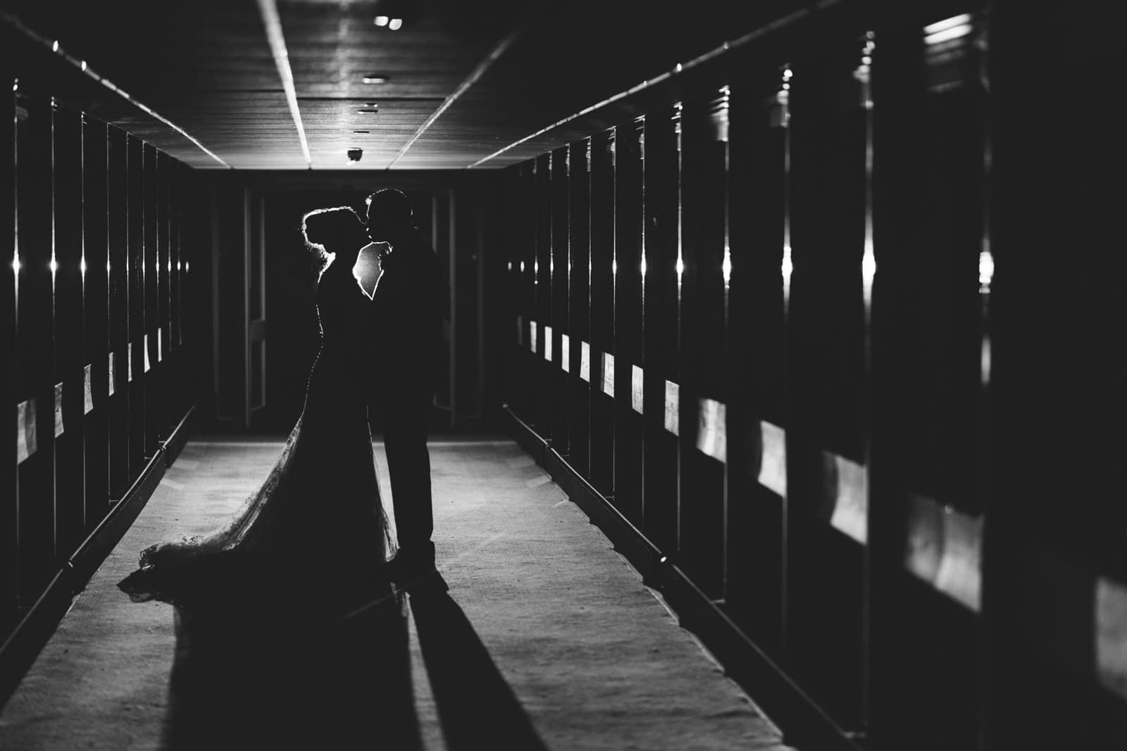 Atmospheric photo of a bride and groom kissing in a corridor.
