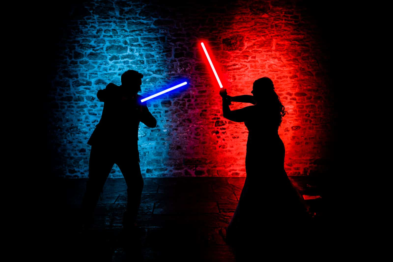 Star Wars Themed Wedding photo of Couple playing with lightsabers
