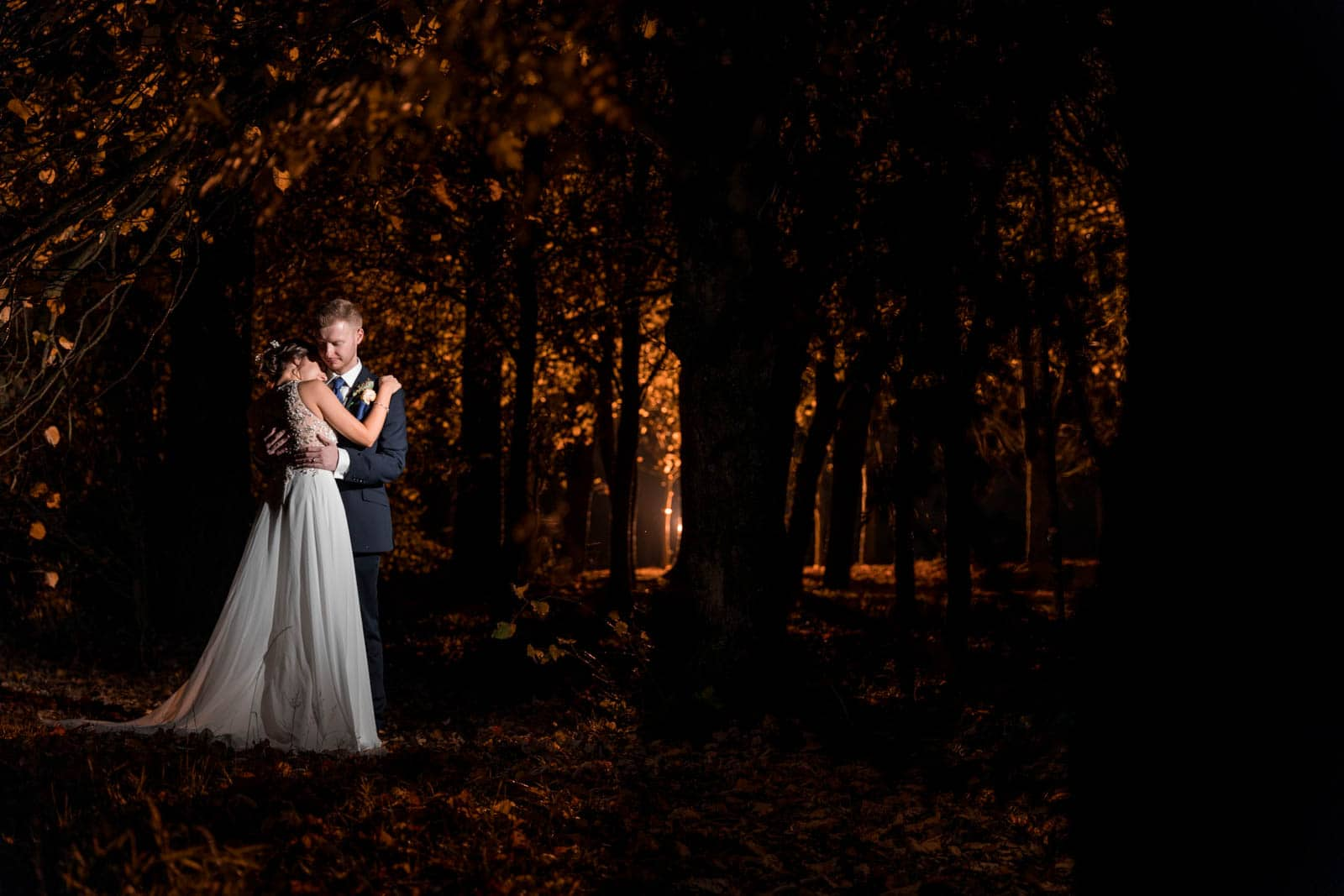 Beautiful ethereal wedding photo of the bride and groom standing in the woods
