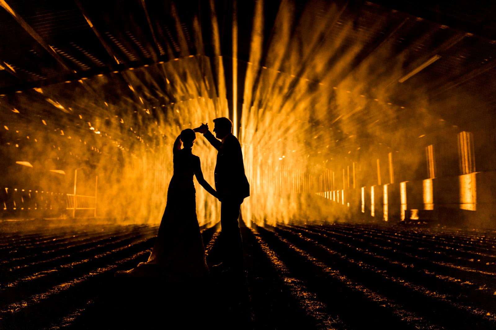 Stunning wedding silhouette photo of a couple in a barn at night, photo taken at Wood Farm Everdon