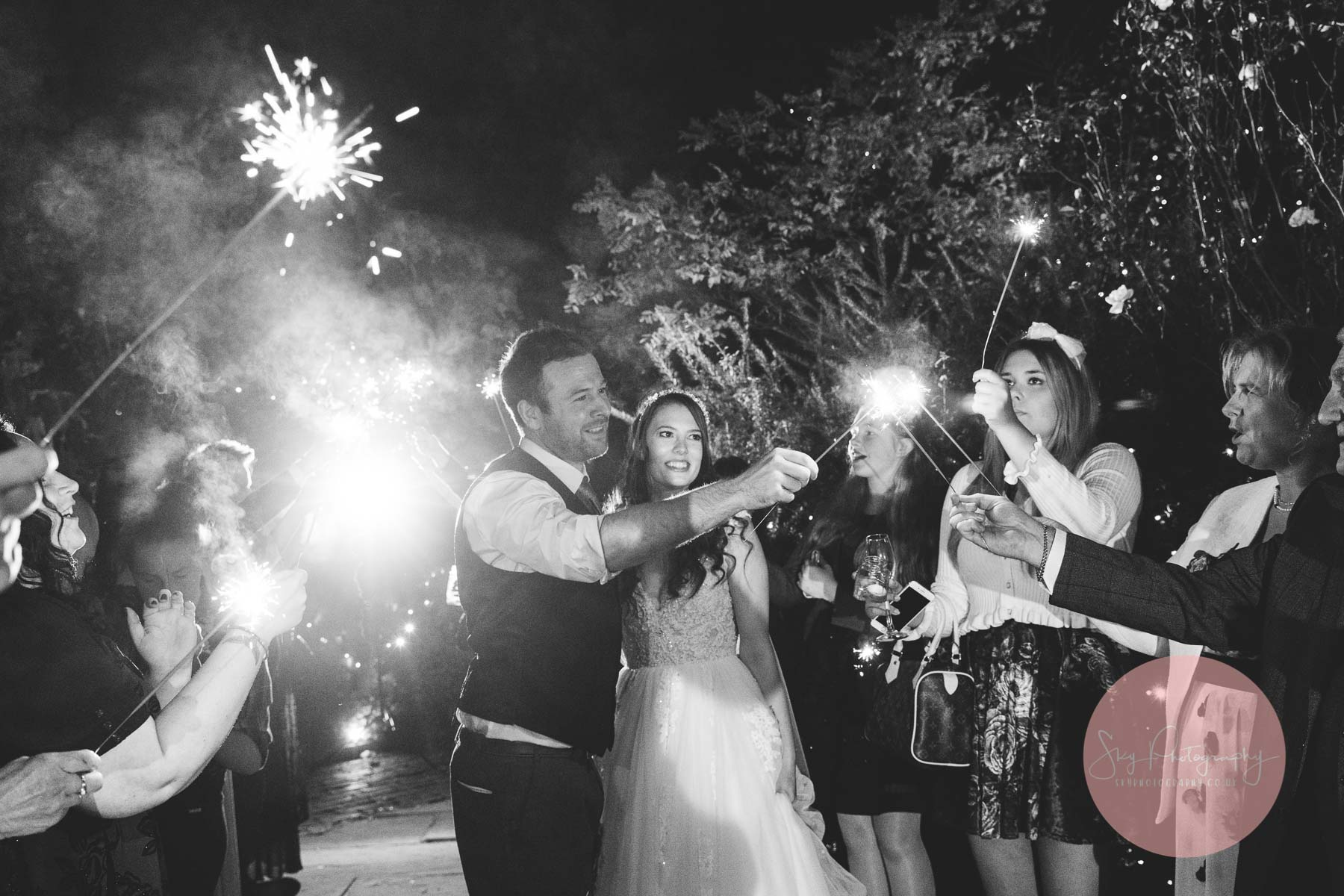 groom reaching for a sparkler with his bride in his arms