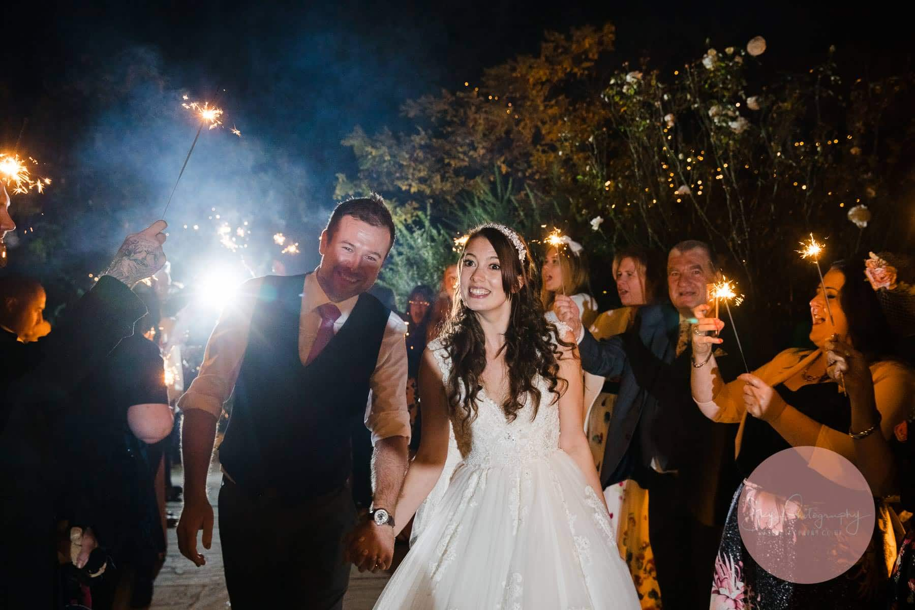 Bride and groom walking though the wedding guests holding sparklers