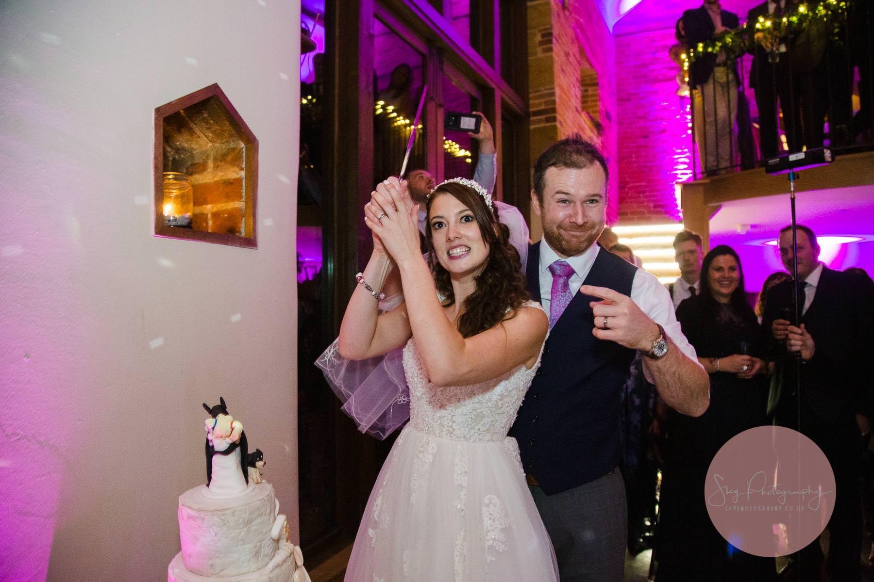 funny moment as the bride holds the knife ready to cut the cake