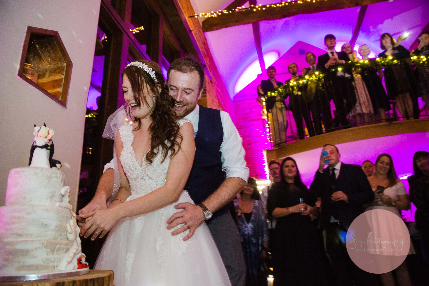 bride and groom holding a knife and cutting the cake