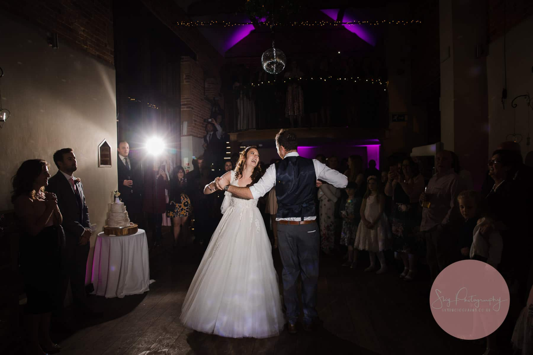 first dance at dodmoor house with the guests standing on the mezzanine