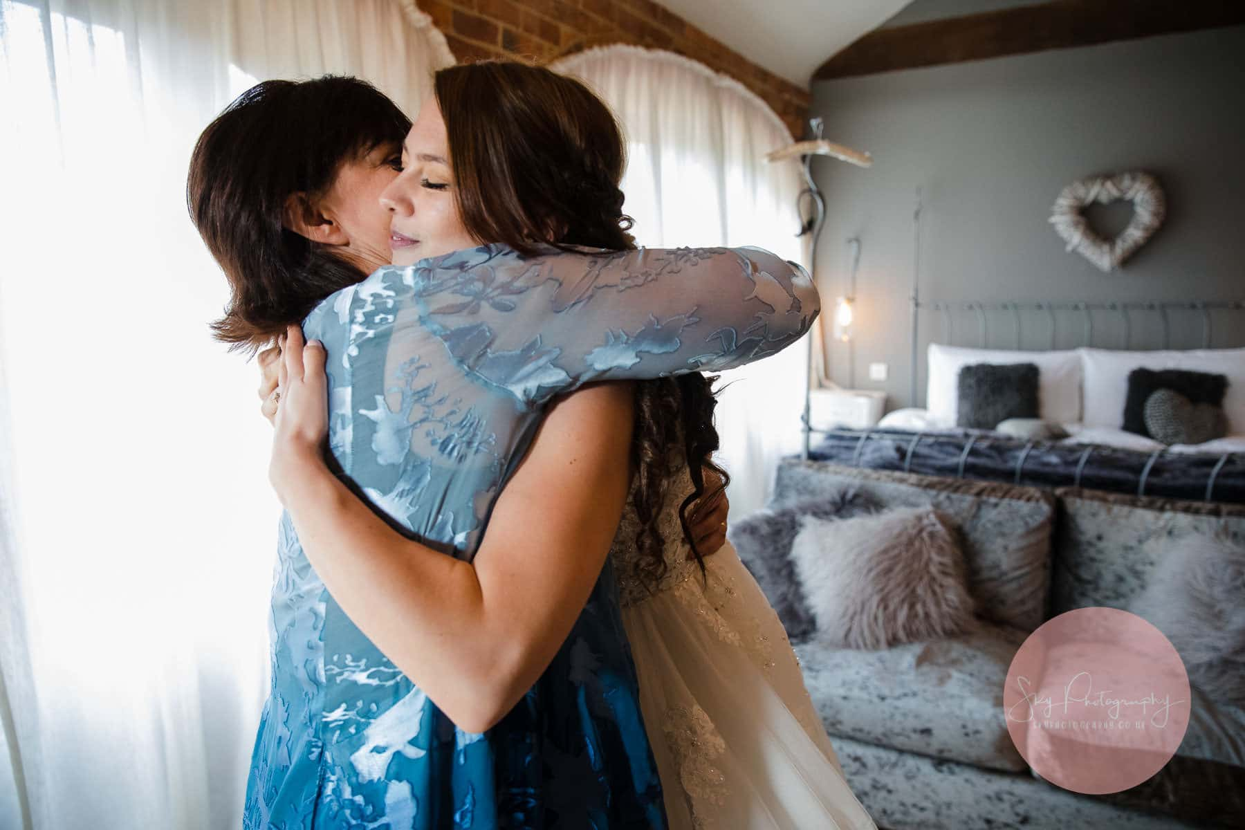 mother emotionally embraces her bride daughter after seeing her in her dress for the first time