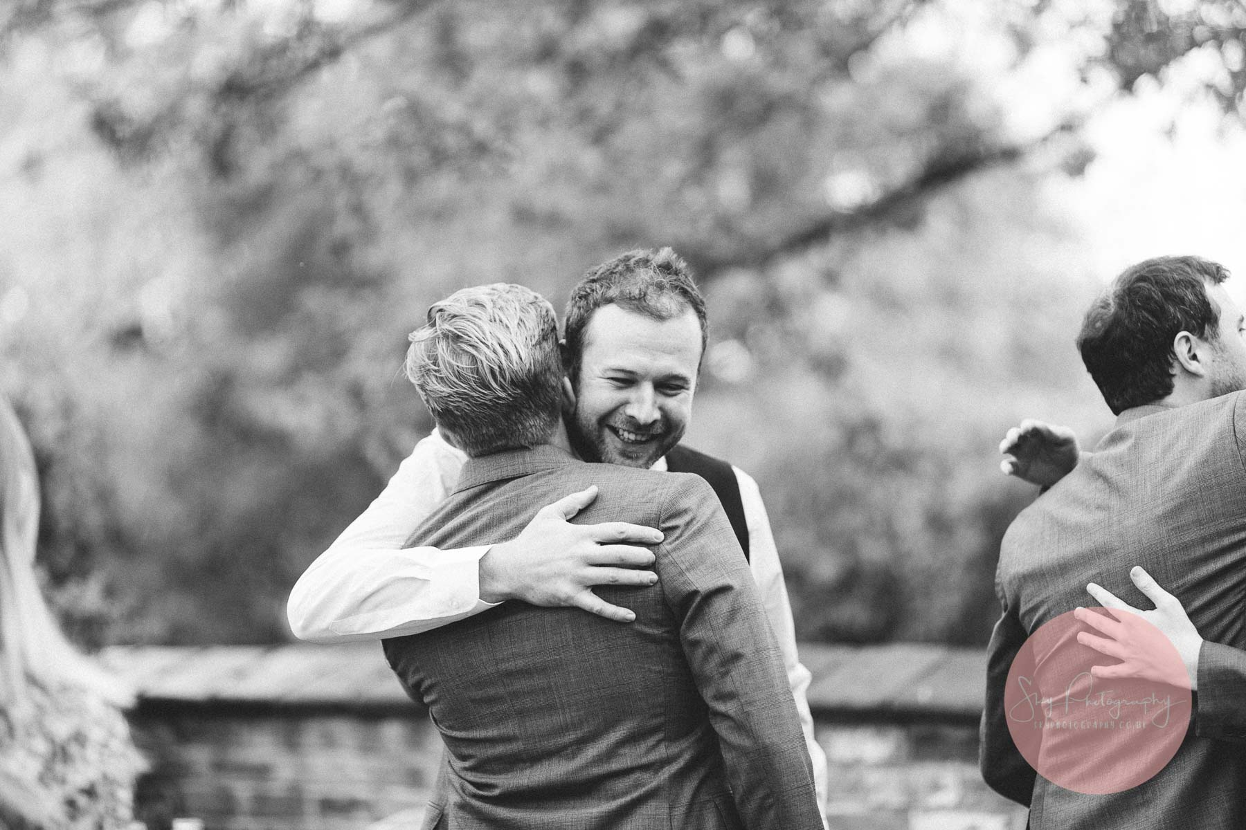 groom embraces a wedding guests