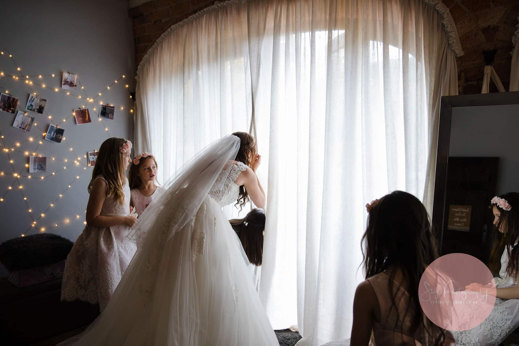 bride catches a sneaky look at her groom through the curtain