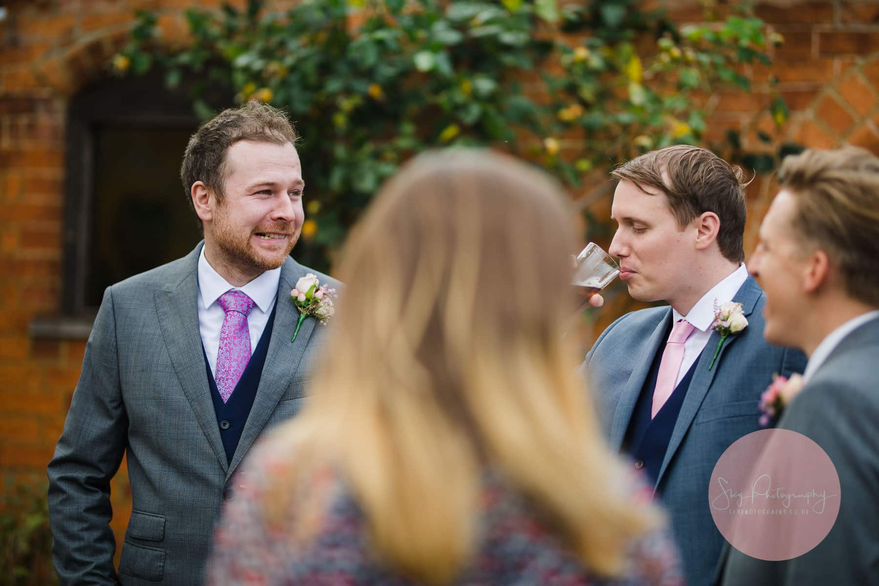 groom nervously smiles whilst greeting his guests