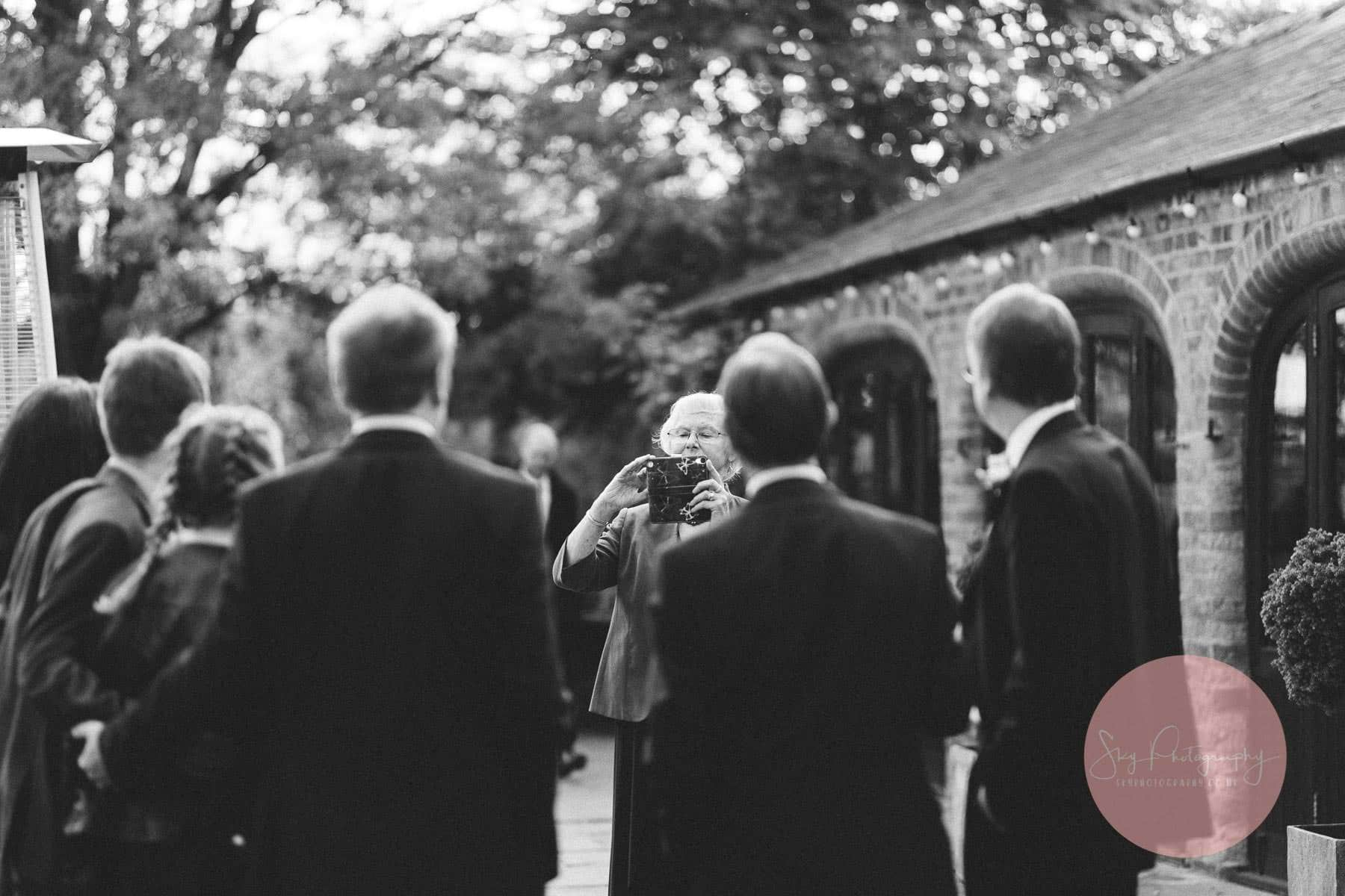 grndma taking a photo of wedding guests