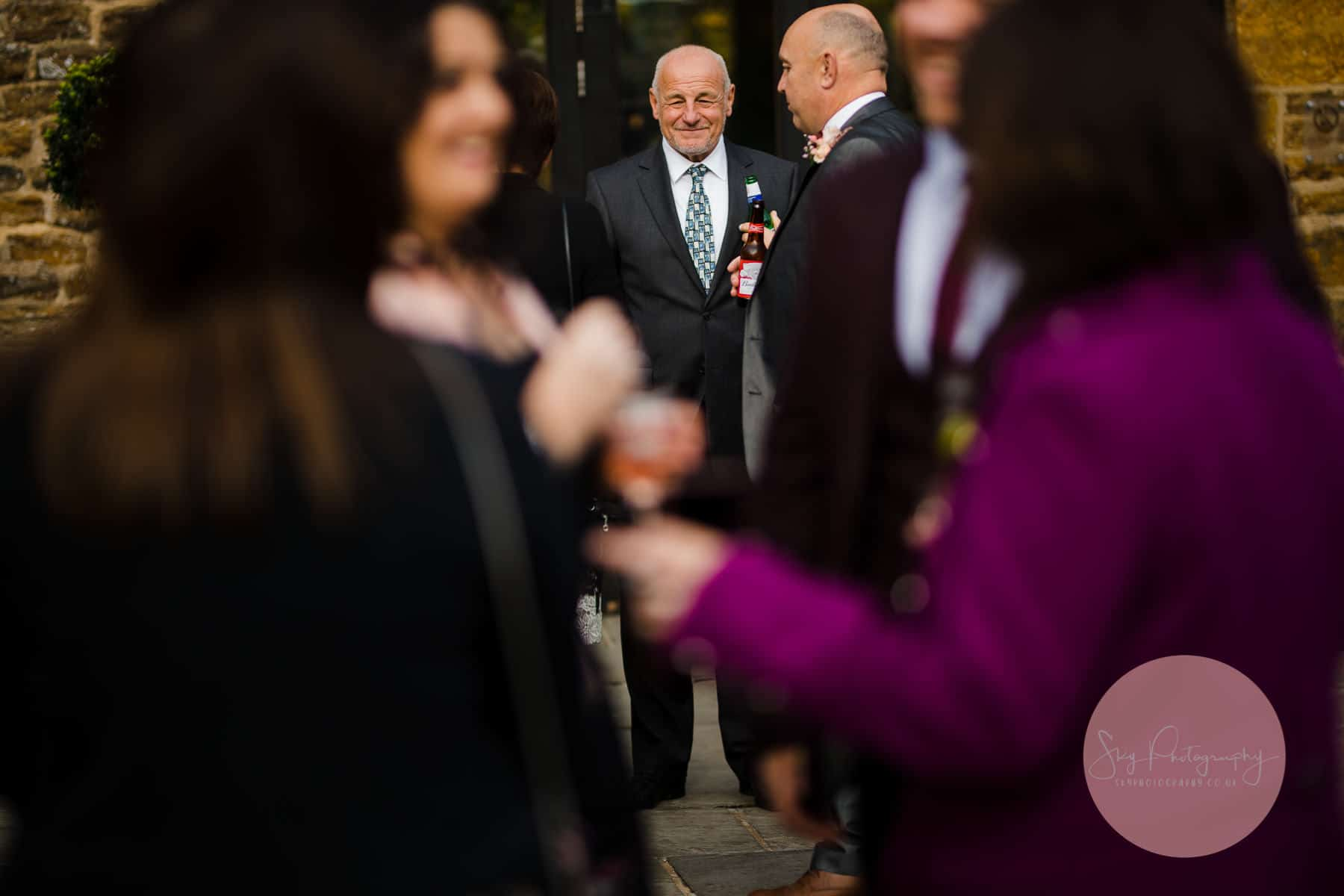 man standing in a crowd at a wedding reception