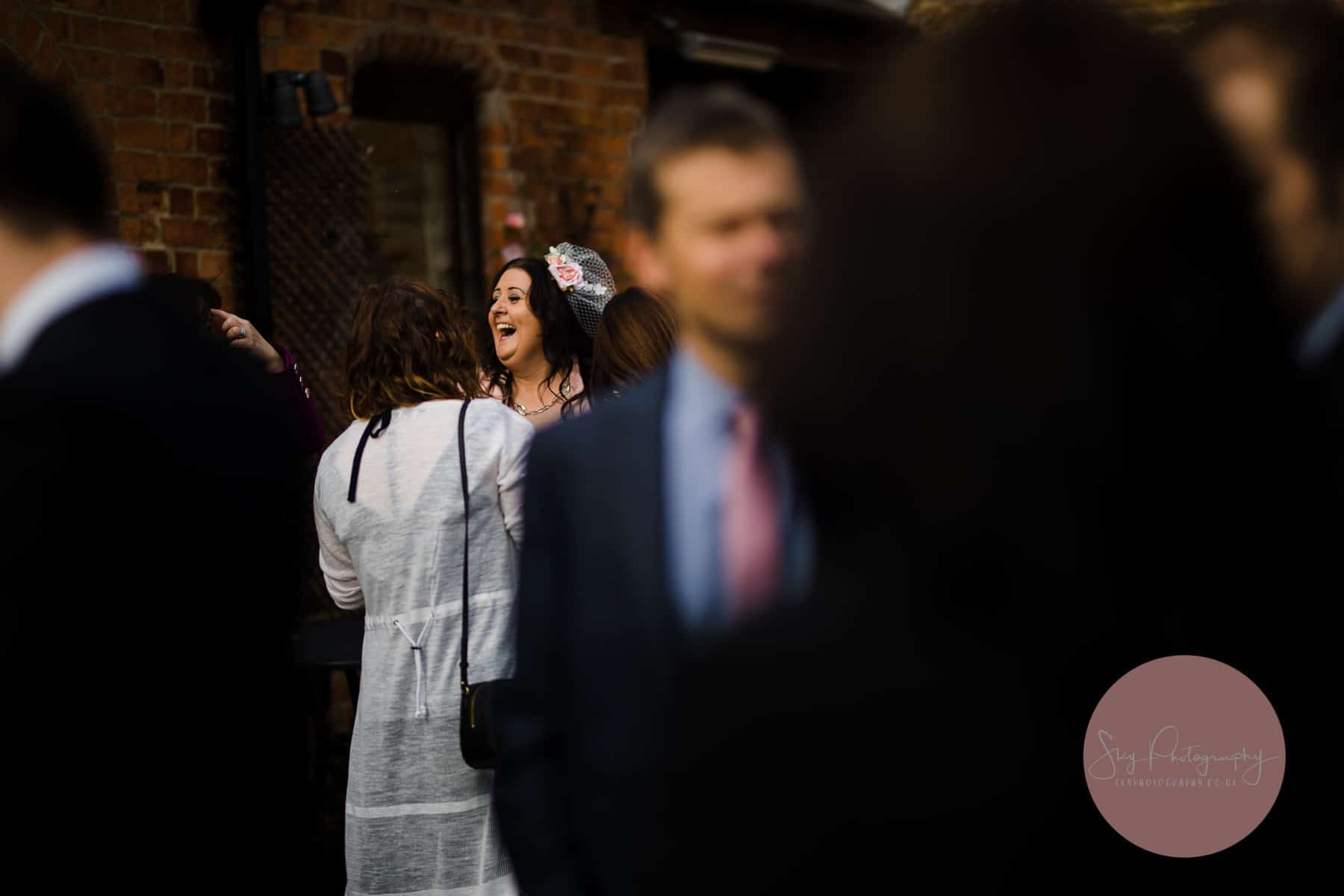 wedding guest laughing at her own joke