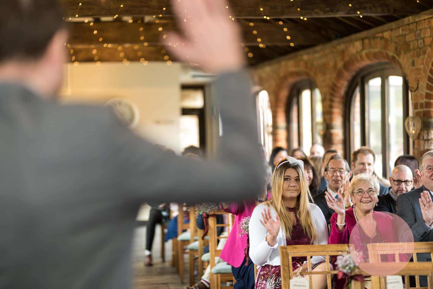 groom issues one last goodbye to his guests and they respond with a wave