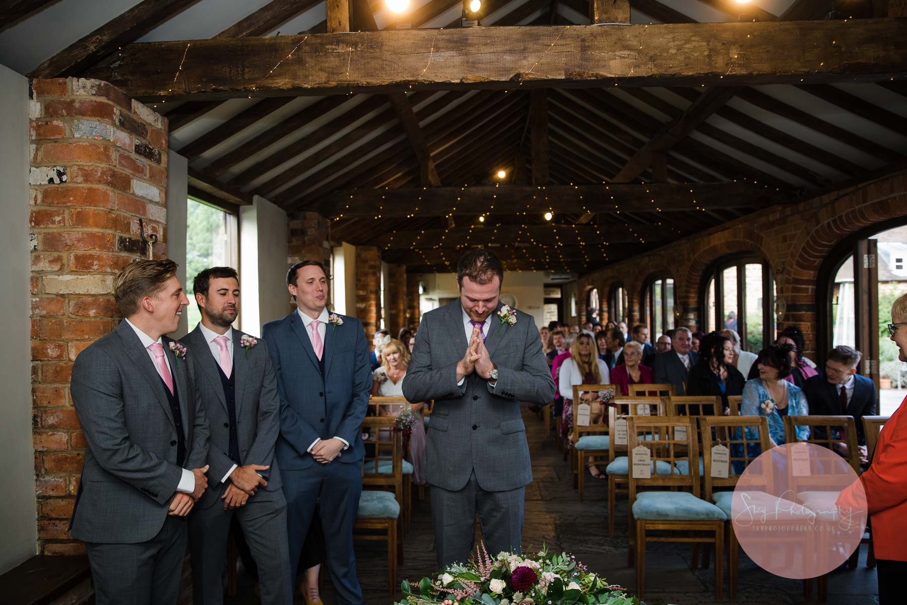 grooms men and groom await the arrival of the bride
