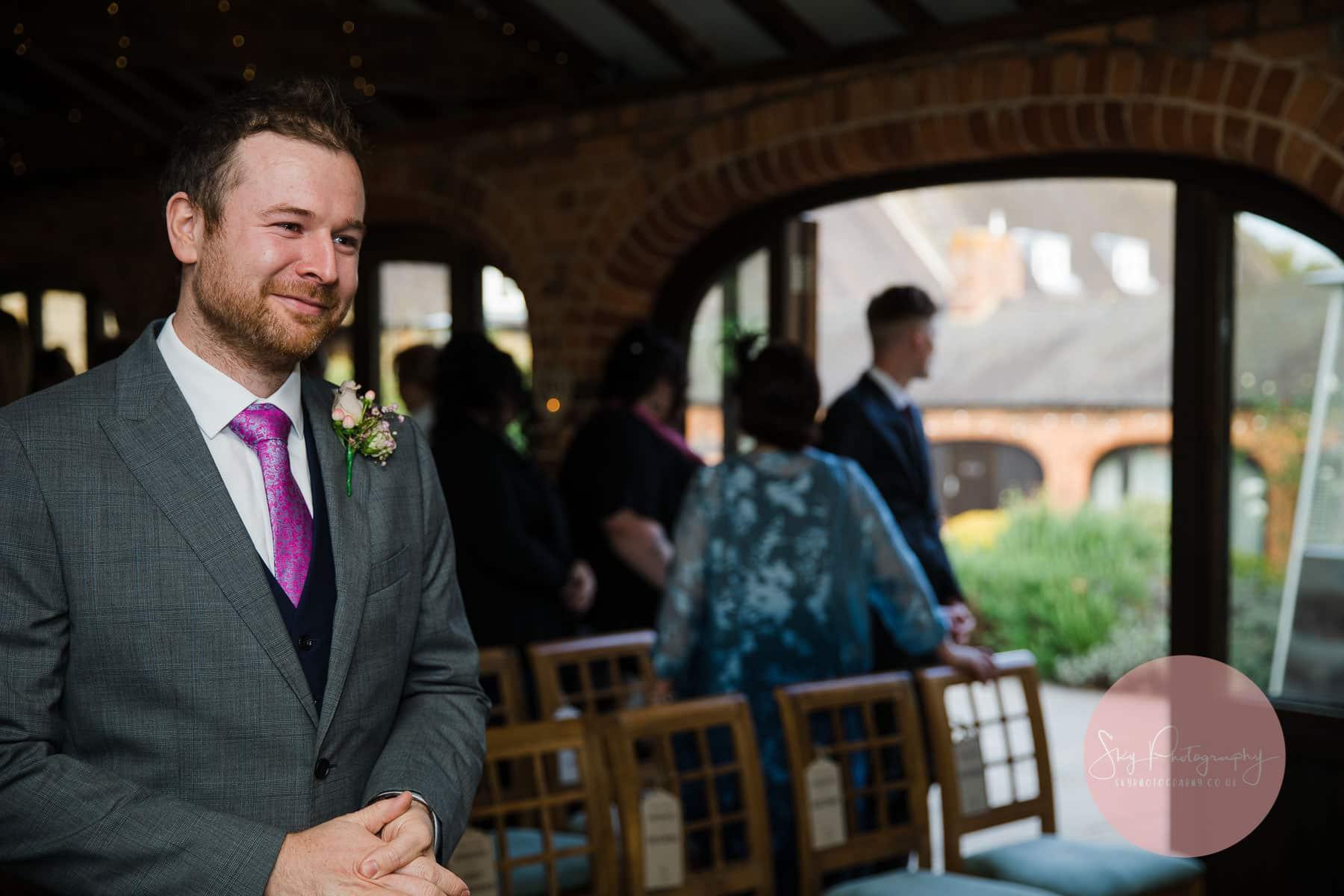 nervous and emotional groom awaits his brde