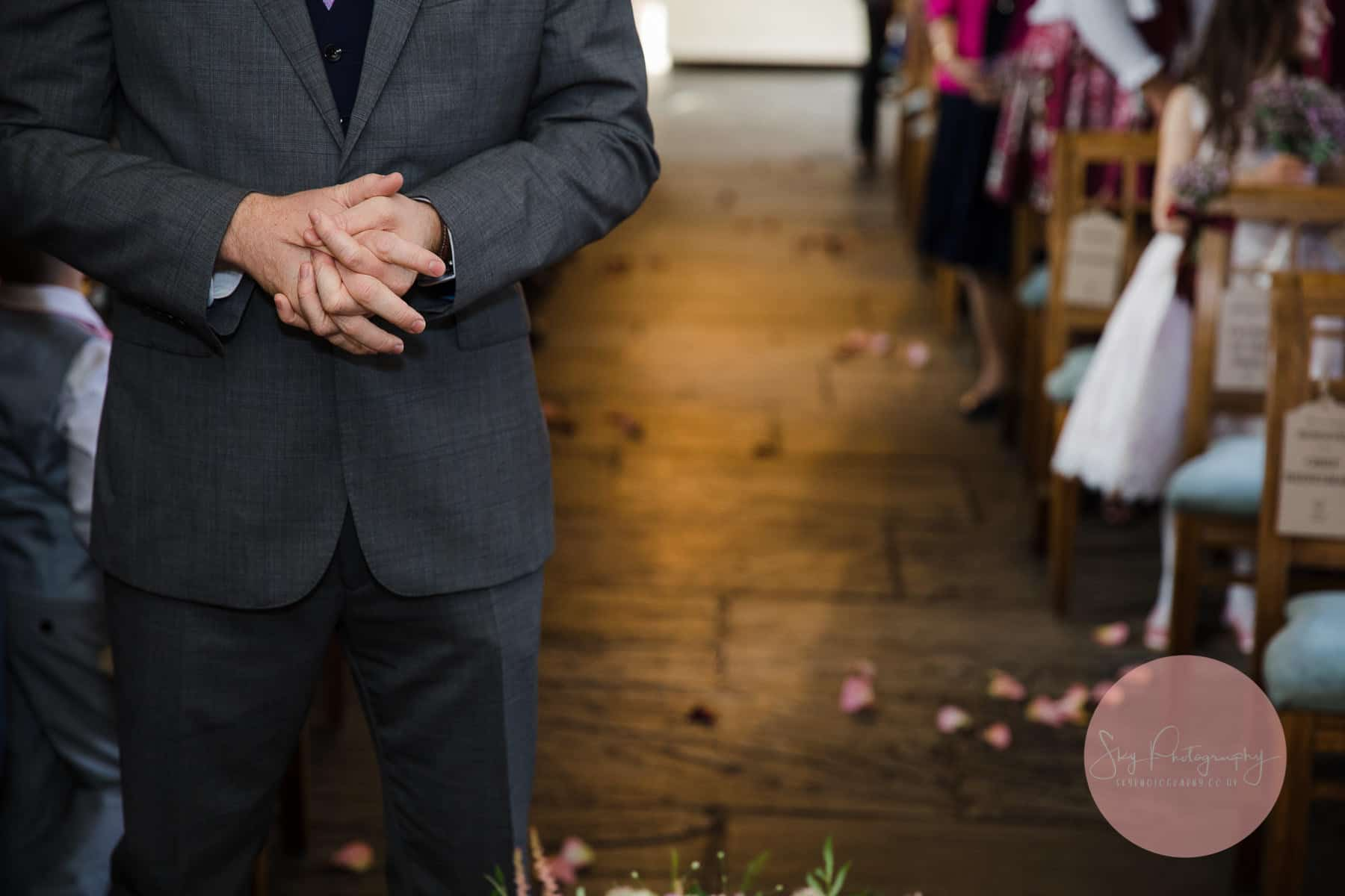 Groom nervously waits for the arrival of the bride, his hands nervously being rung
