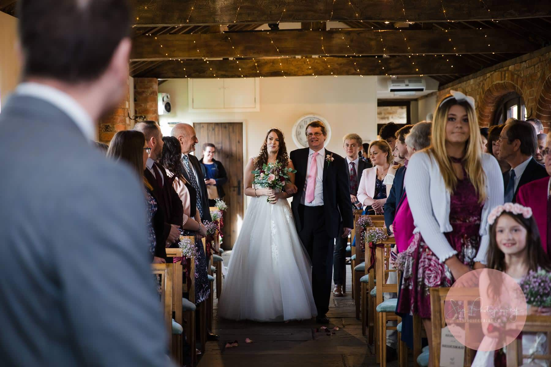 bride walking down the aisle with her guests looking on