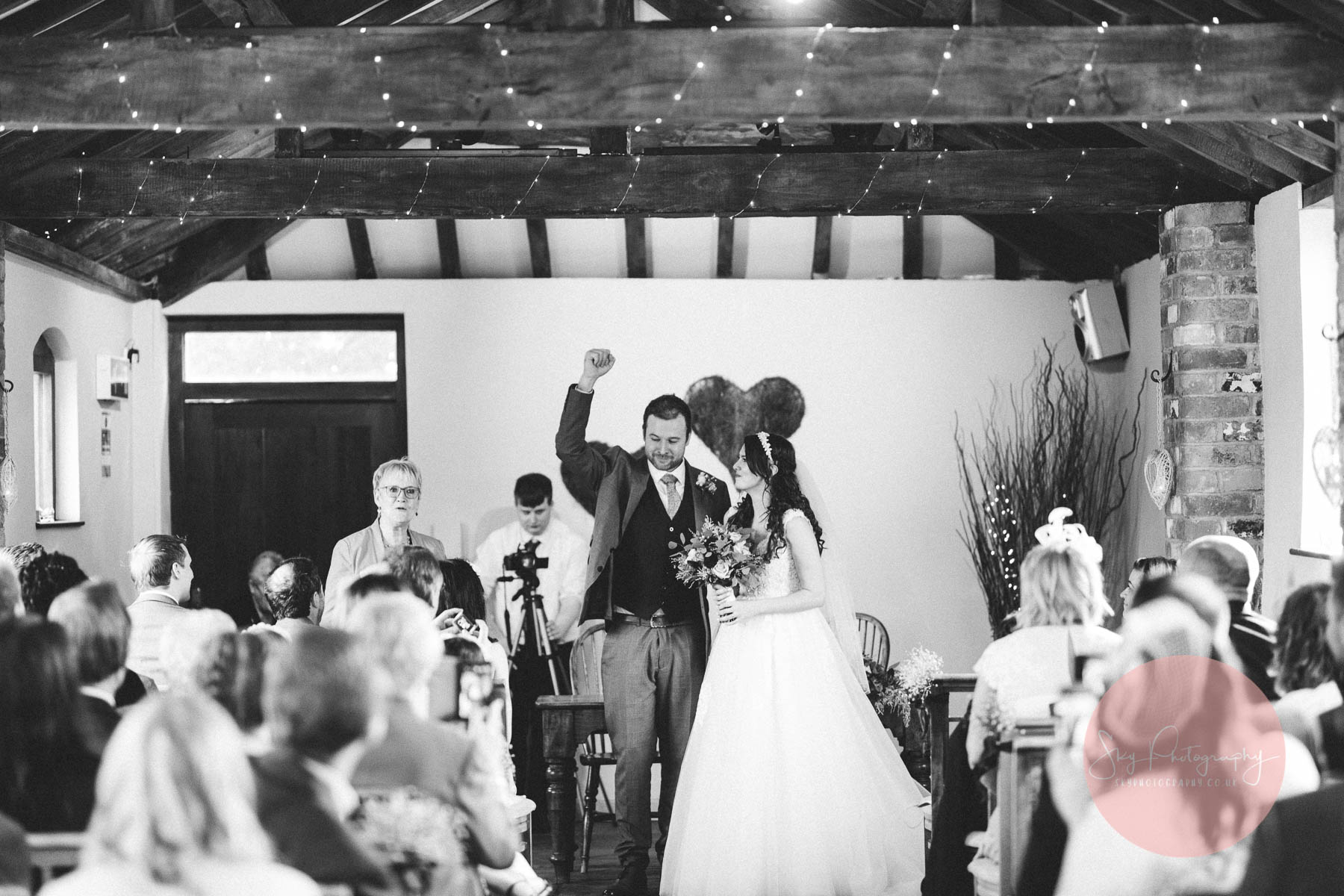 groom has his hand aloft as he celebrates getting married
