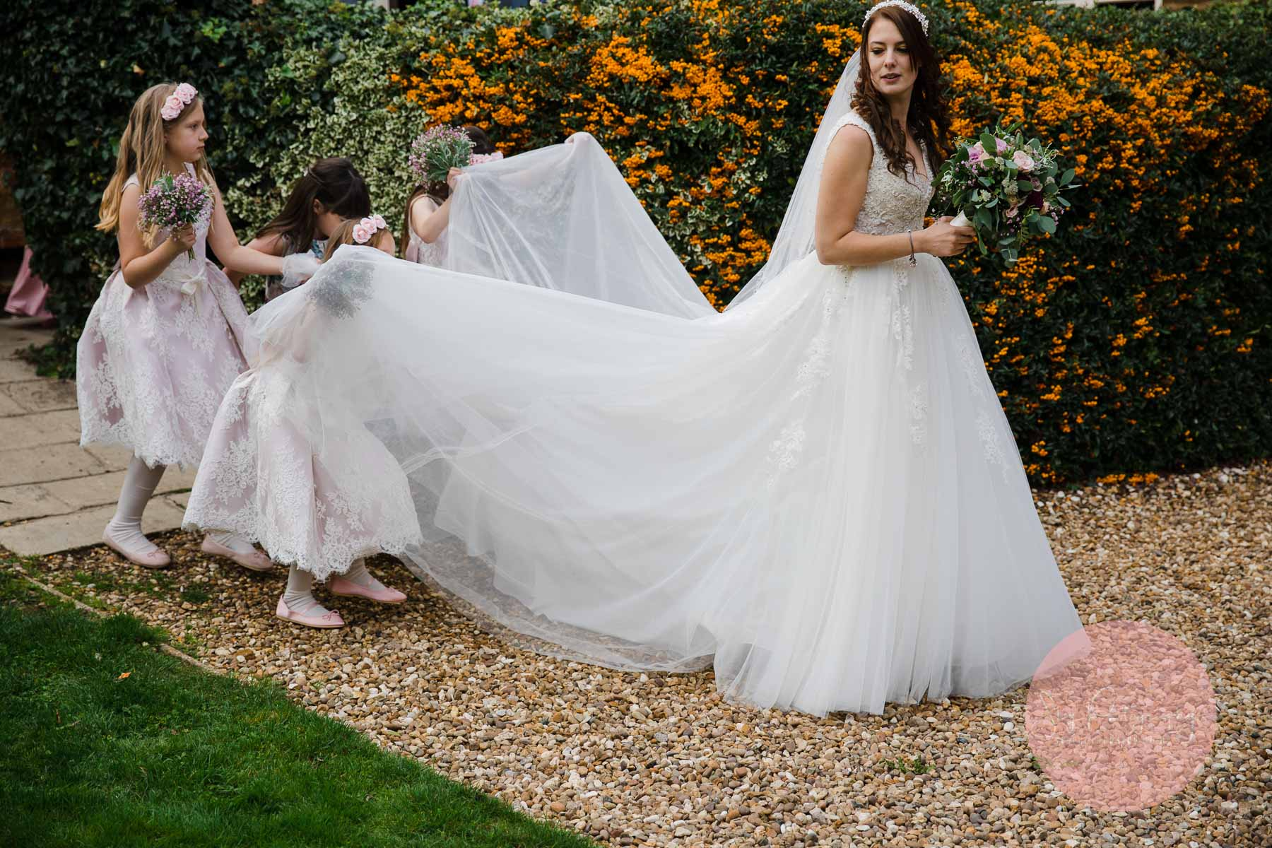 brides dress being carried by flower girls