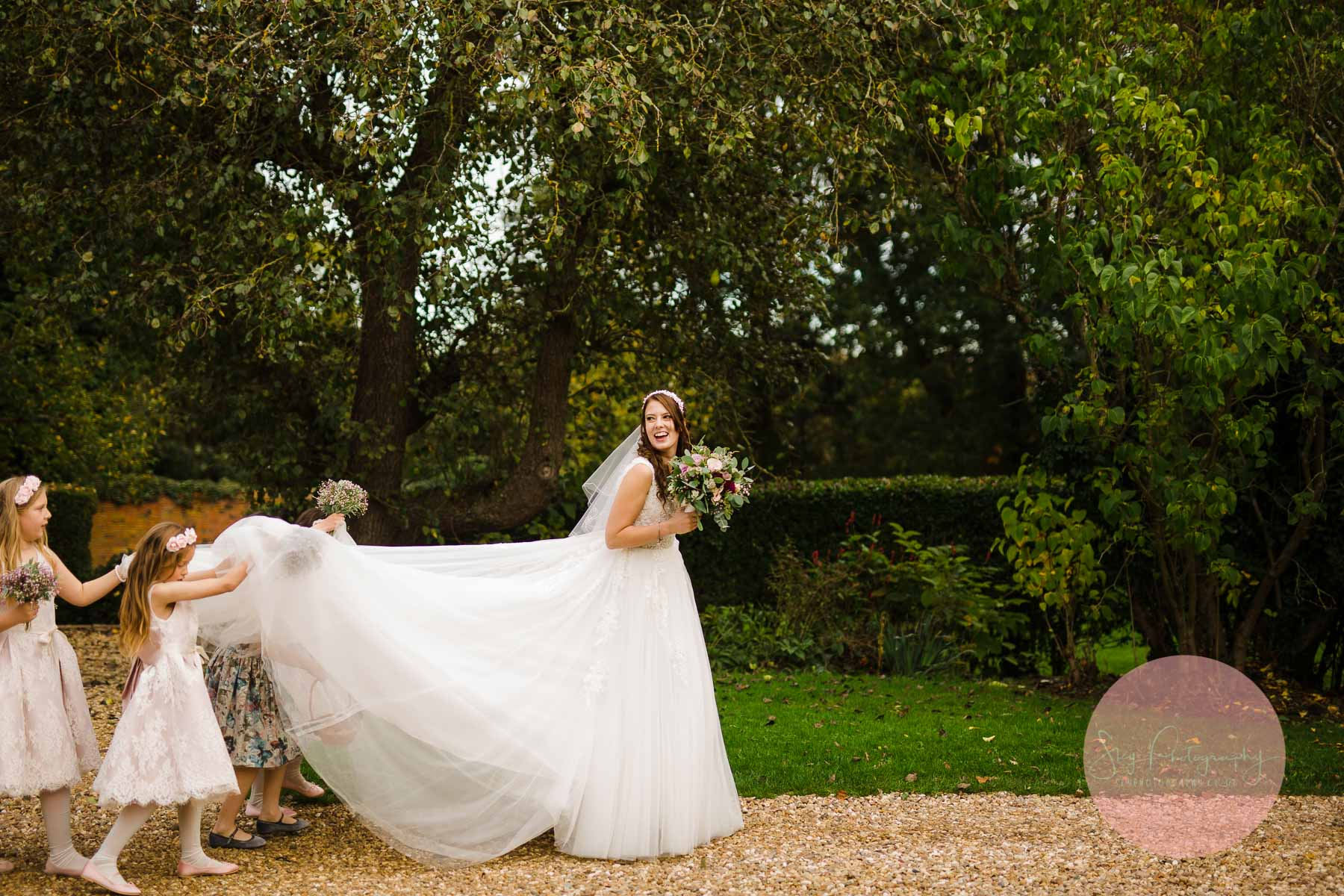 flower grils and bridesmaids carrying brides dress
