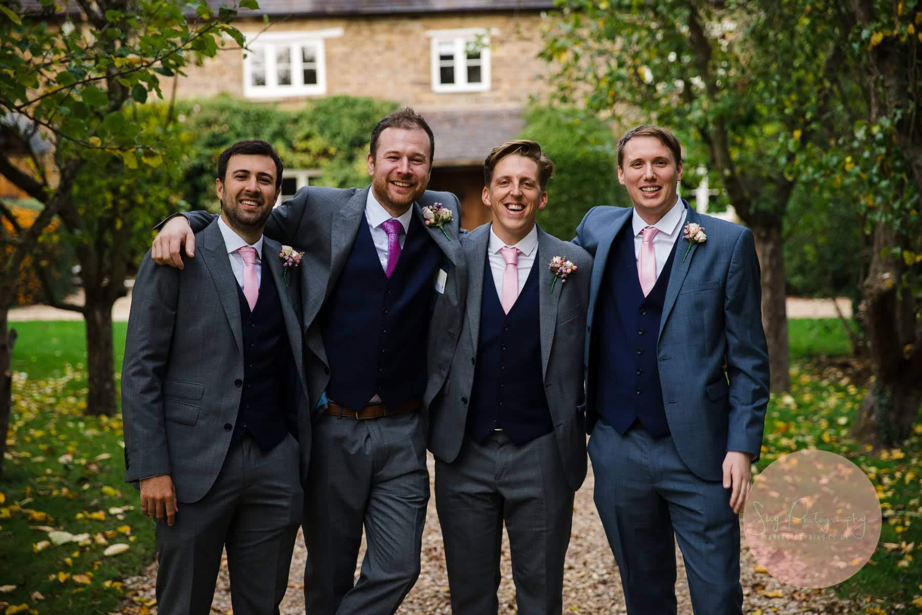 grooms men smiling posing for formal photos