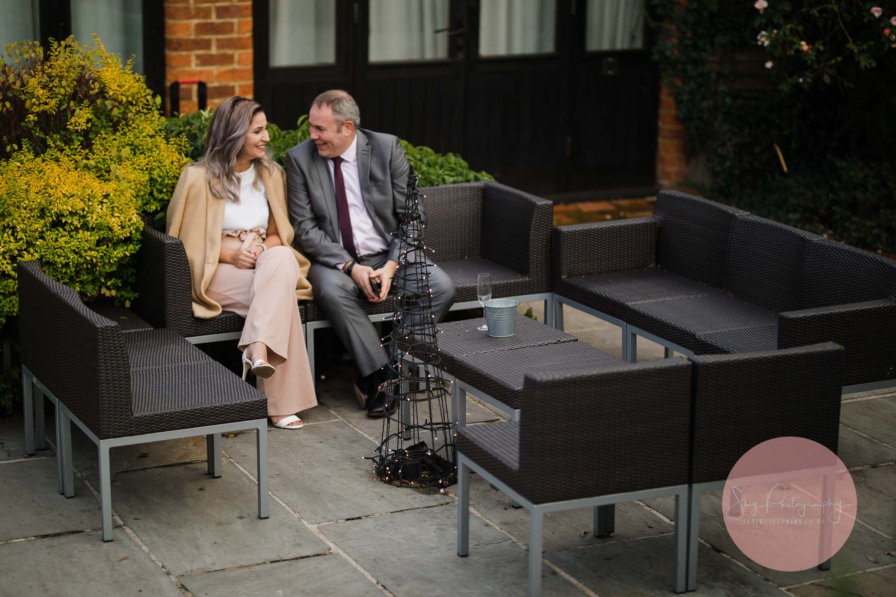 wedding guests enjoying a laugh whilst sitting on a bench