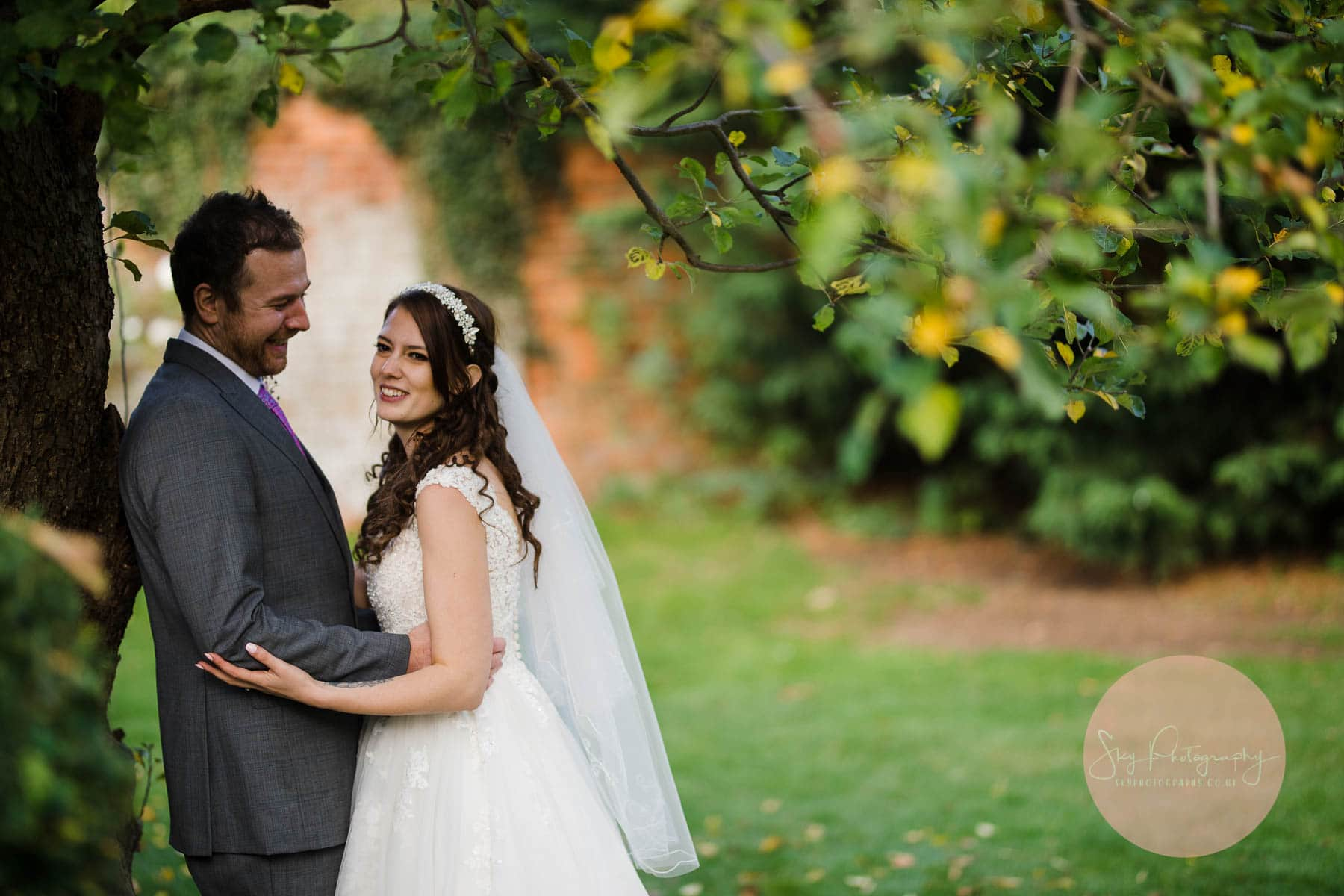 Couple standing under a tree in the grounds of the venue