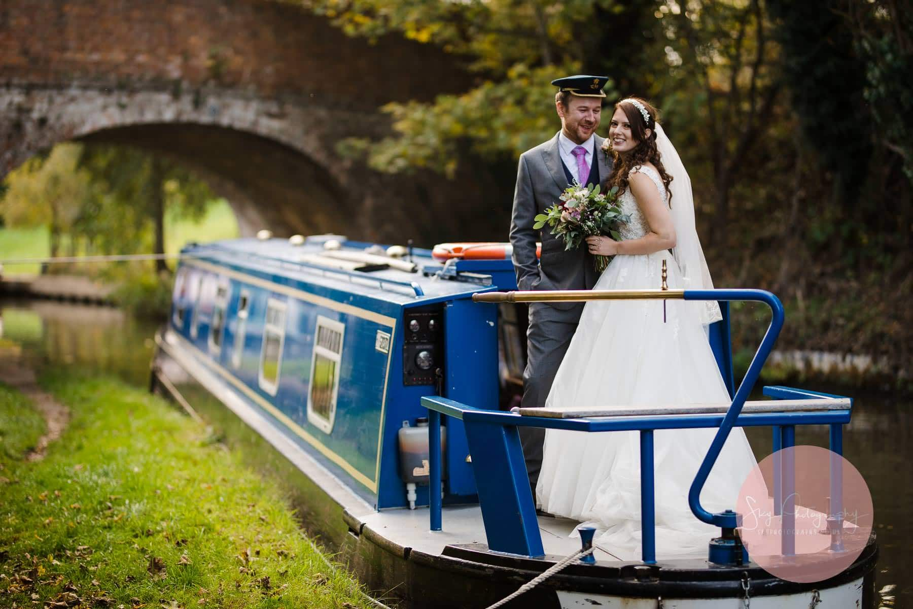 bride and groom get a lift on a canal boat a gret wedding moment