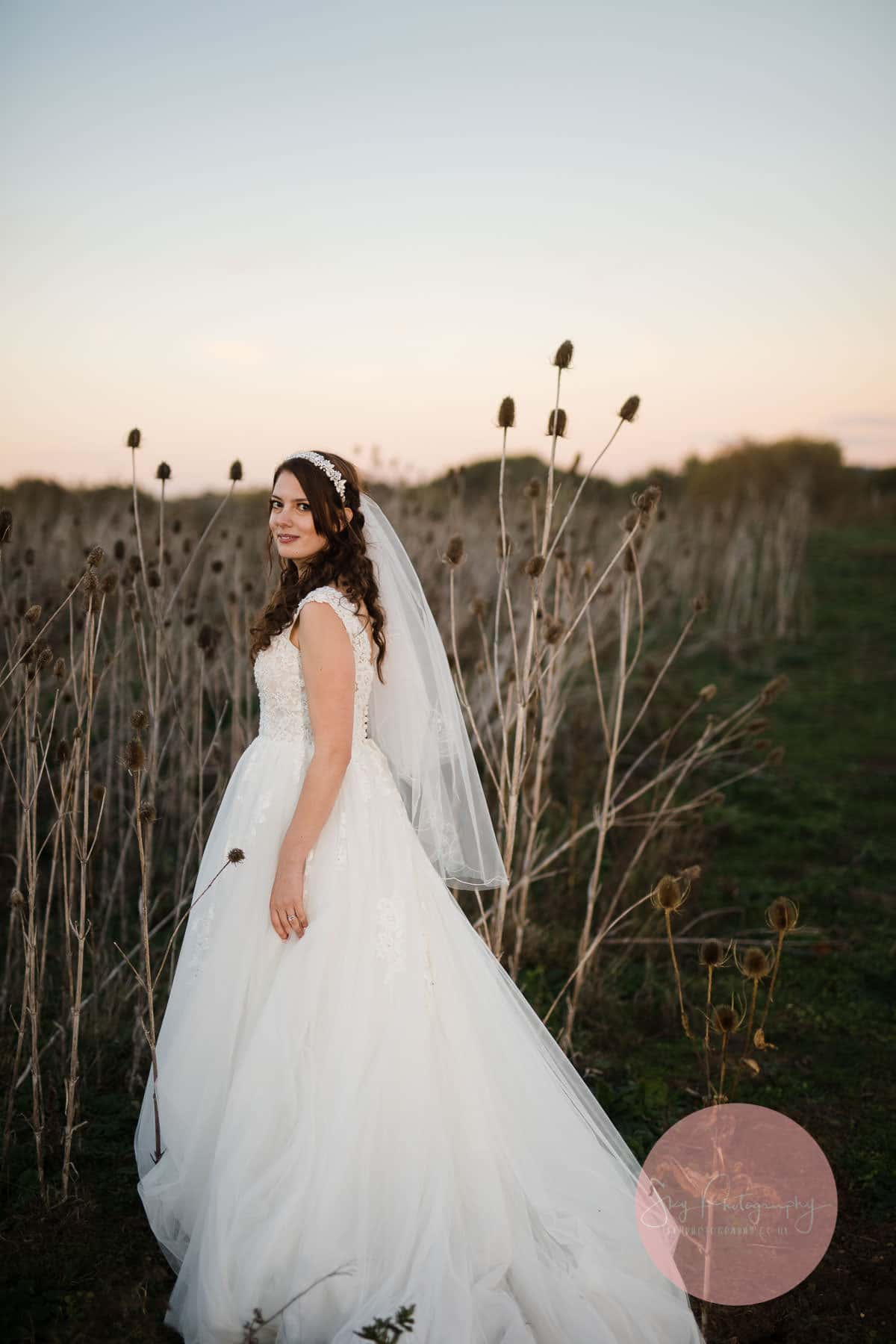 Bride standing next to thistles looking beautiful