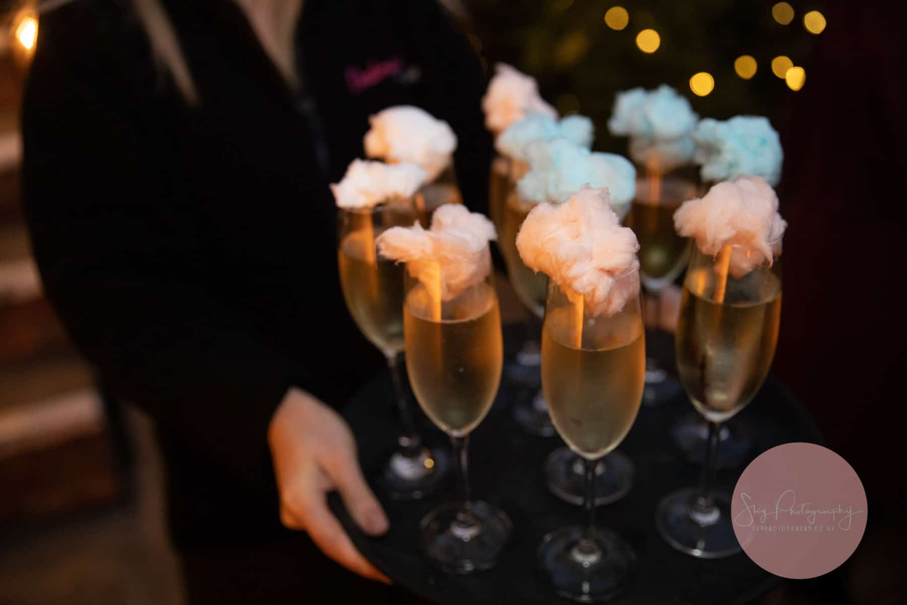 Prosecco being served with candy floss pom poms on top at Dodmoor house