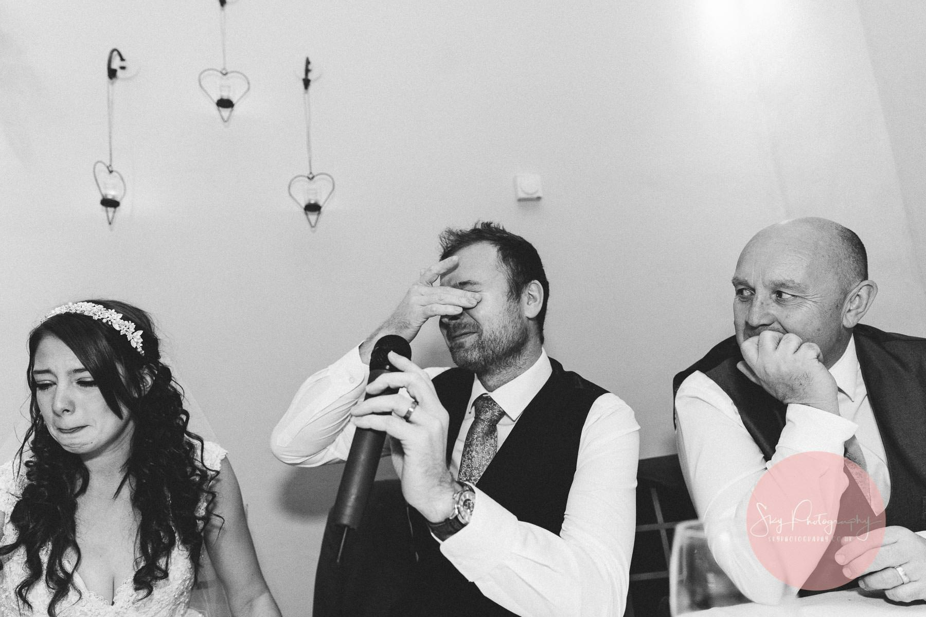 Emotional groom delivering a perfect speech and the bride in tears of happiness